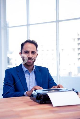 Portrait of smiling businessman working on typewriter  at office