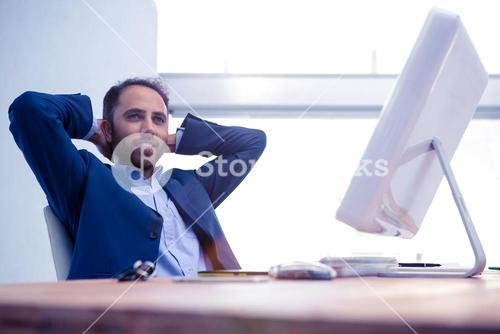 Businessman relaxing with hands behind head in office