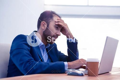 Bored man working on laptop in office