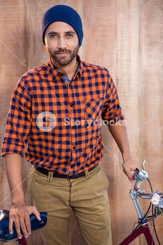 Portrait of businessman standing with bicycle in office