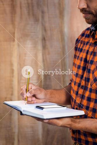 Businessman with smartphone writing on book