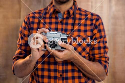 Mid section of businessman holding camera against wall