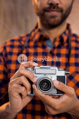 Mid section of businessman holding camera against wall in office