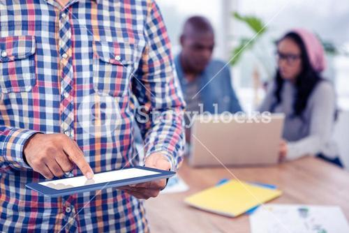 Mid section of business man using digital tablet