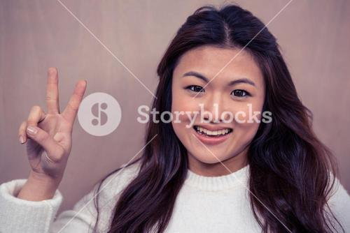 Smiling Asian woman making peace sign