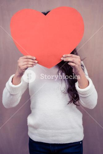 Woman hiding her face behind paper heart