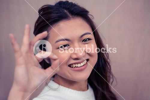 Smiling woman making ok sign with hand