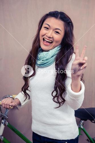 Asian woman holding bike and making peace sign with hand