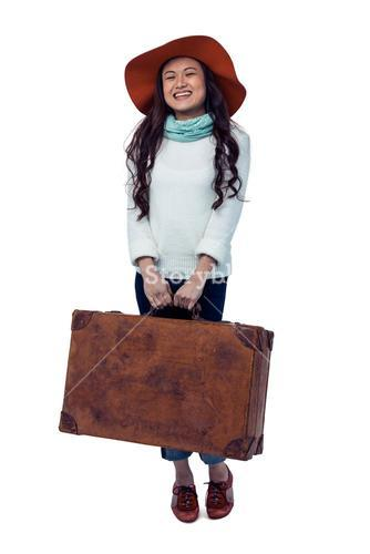 Smiling Asian woman holding luggage