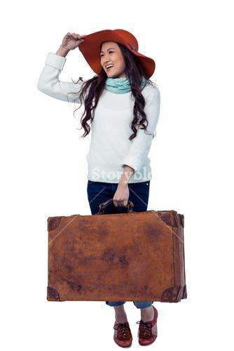 Smiling Asian woman holding luggage holding hat
