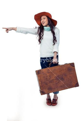 Smiling Asian woman holding luggage pointing somewhere