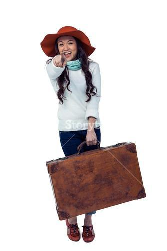 Smiling Asian woman holding luggage pointing the camera