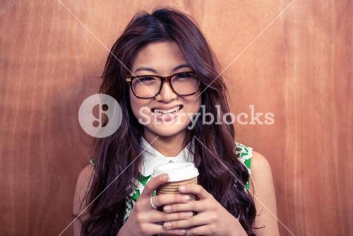 Smiling woman holding disposable cup