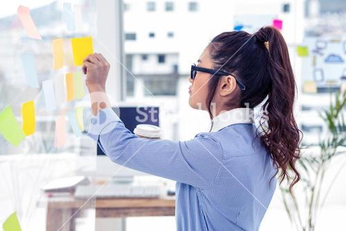 Businesswoman holding disposable cup and looking at wall with notes