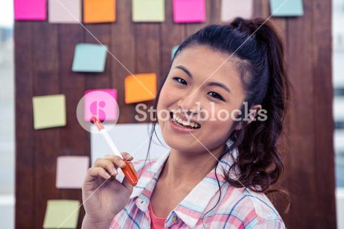 Smiling woman against wooden wall with notes on it