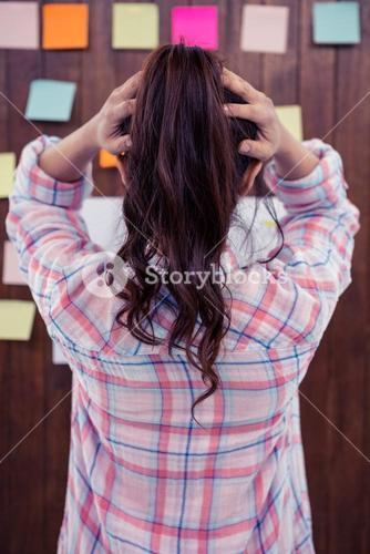 Brunette with hands on hair in front of sticky notes on wooden wall