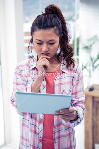 Thoughtful woman with finger on chin holding tablet