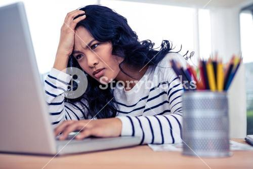 Concentrated Asian woman with hand on head using laptop