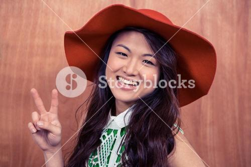 Smiling Asian woman doing peace sign with hand