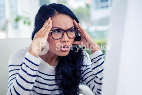 Frowning Asian woman looking at laptop with hands on head