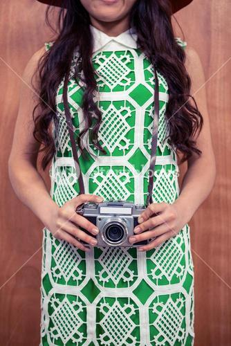 Mid section of woman holding camera