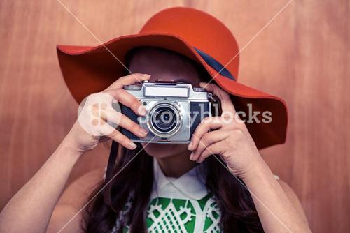 Woman with hat taking photograph with camera