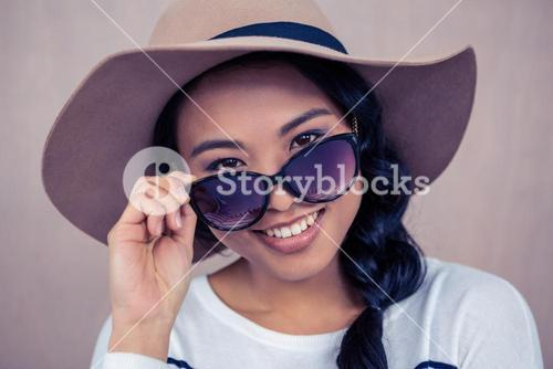 Smiling Asian woman with hat and sunglasses