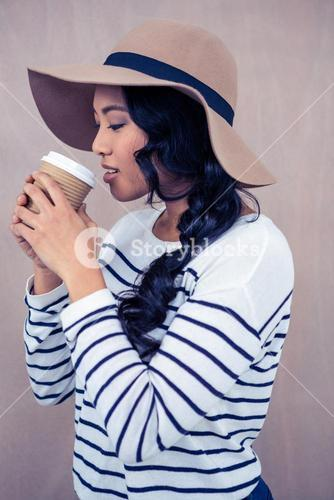 Attractive woman with hat holding disposable cup