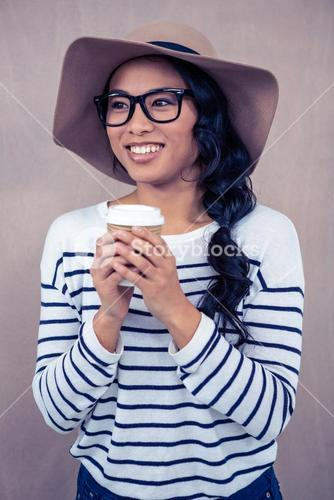 Attractive Asian woman with hat holding disposable cup