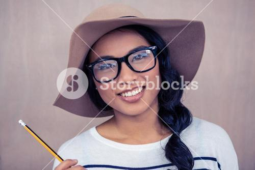 Smiling Asian woman with hat holding pencil