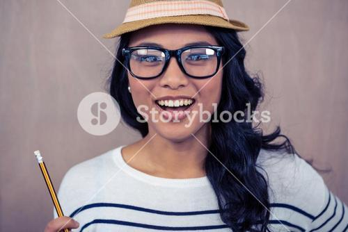 Attractive Asian woman with hat holding pencil