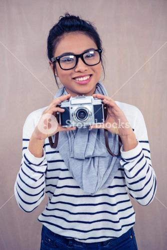 Smiling Asian woman holding camera