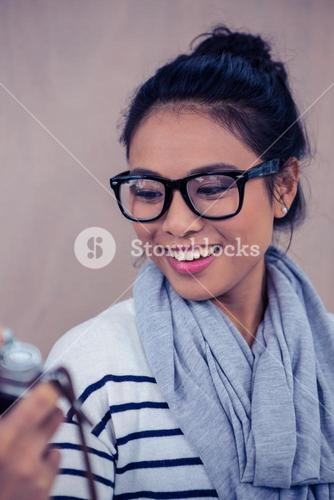 Smiling Asian woman taking selfie with camera