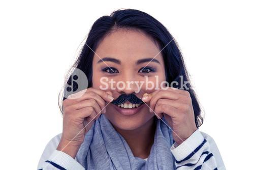 Pretty Asian woman with fake mustache posing for camera