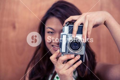 Smiling Asian woman taking photograph with camera