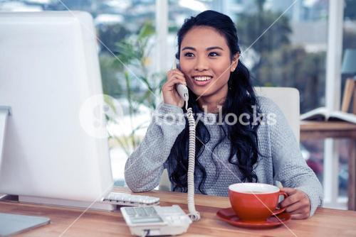 Smiling Asian woman on phone call holding mug