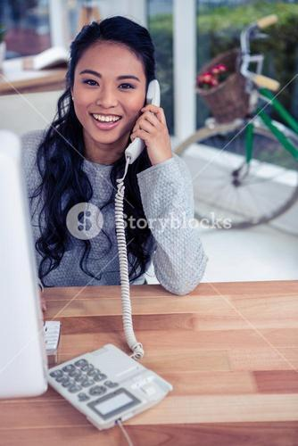 Smiling Asian woman on phone call looking at the camera
