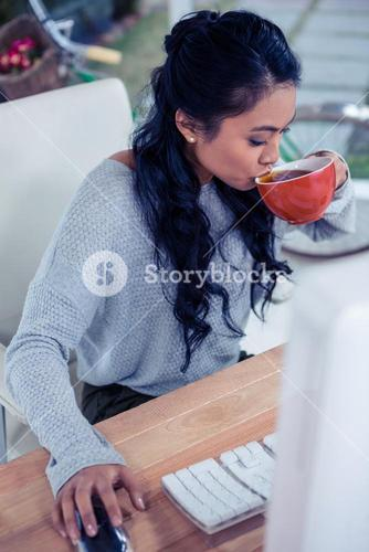 Pretty Asian woman using computer and drinking by cup