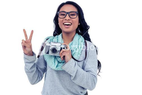 Asian woman holding digital camera and making peace sign with hand