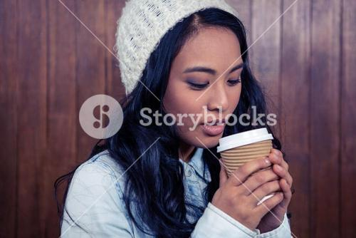 Asian woman holding disposable cup