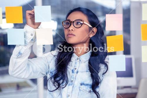 Asian woman looking at sticky notes