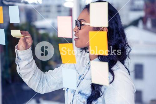 Asian woman removing sticky notes