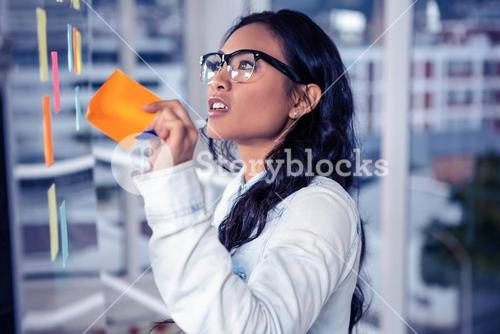 Asian woman removing sticky note