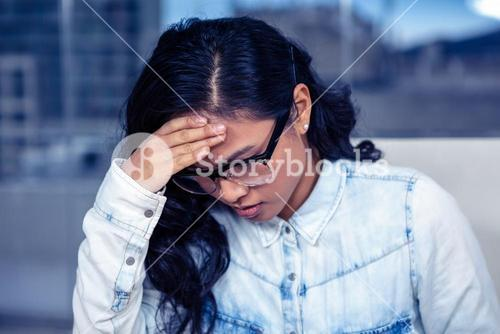 Troubled Asian woman with hand on face