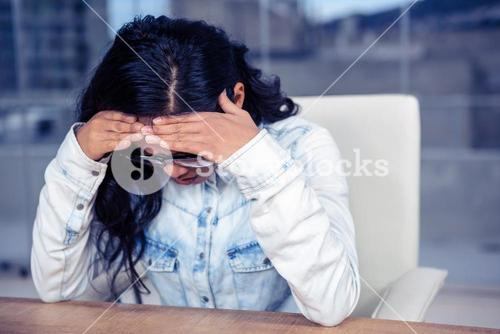 Troubled Asian woman with hands on face