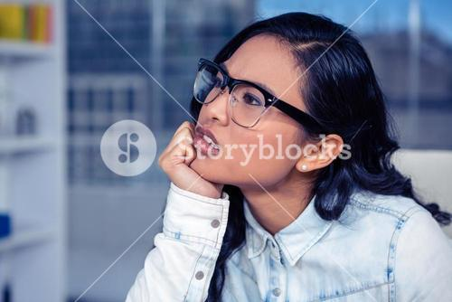 Troubled Asian woman with chin on fist