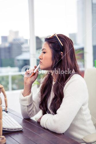 Focused Asian woman with pen on chin