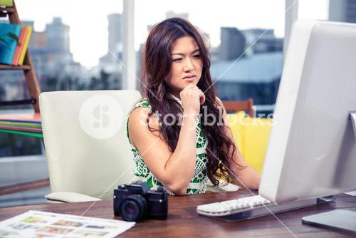 Focused Asian woman using computer with hand on chin