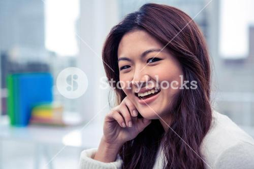 Smiling Asian woman with hand on cheek
