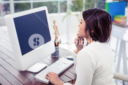 Asian woman on computer with finger on chin